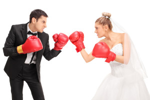 Young groom and a bride fighting each other with boxing gloves i