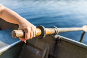 Female Hand On Row Boat Oar Closeup In Summer With Water