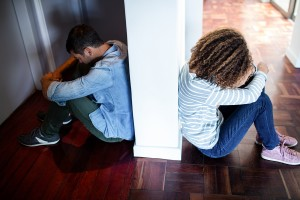 Couple sitting on opposite sides of the wall and feeling sad