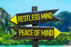 Restless Mind - Peace of Mind signpost in a beach background
