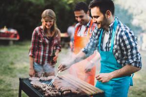 Friends having fun grilling meat enjoying bbq party